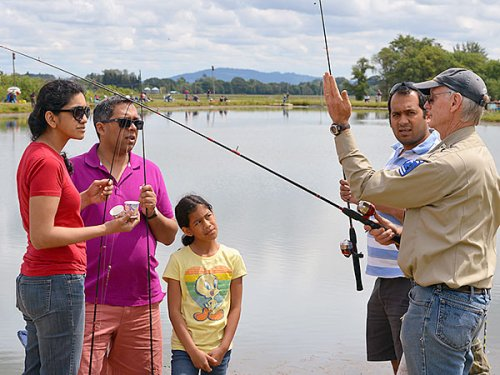 ODFW volunteer angling instructor Jack Morby goes over the basics of trout fishing with Sunil, Carol